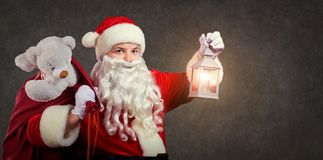 Santa Claus with a bag and a lamp on a Christmas. stock image