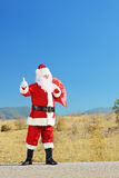 Santa claus with bag on an open road hitchiking Stock Photography