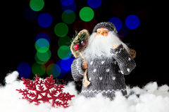 Santa Claus with bag of presents on the black background. With colorful bokeh Royalty Free Stock Image