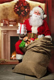 Santa Claus with a bag of presents at the fireplace Royalty Free Stock Photo