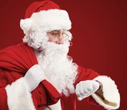 Santa Claus with a bag of presents and looking at his watch. Christmas. Royalty Free Stock Image
