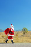 Santa claus with bag walking on an open road Stock Photos