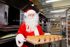 Santa Claus baker with a tray of cupcakes in his hands on Christ Royalty Free Stock Photos