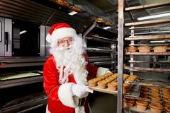 Santa Claus baker with a tray of cupcakes in his hands Christmas Stock Photos