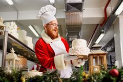 Santa Claus bakes a pie in the kitchen on Christmas Day Royalty Free Stock Images