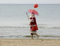 Santa Claus on the beach. Santa Claus with red umbrella walikg along the seaside Royalty Free Stock Image