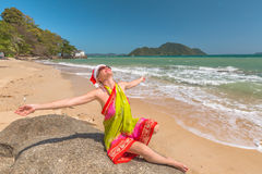 Santa Claus on the beach. Beautiful woman with red Santa Claus hat enjoy and catching tan on rocks in tropical Laem Ka Beach for the Christmas holidays. Phuket stock photography
