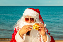 Santa Claus on the beach eating a hamburger. The concept of unhealthy eating royalty free stock photo
