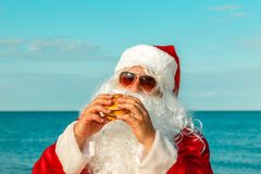 Santa Claus on the beach eating a hamburger. The concept of unhealthy eating royalty free stock images