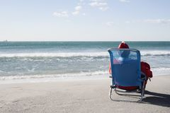 Santa claus on the beach. Santa claus, seen from behind, sitting in a deckchair on the beach facing the horizon stock photography