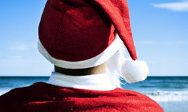 Santa claus on the beach. Santa claus seen from behind on the beach facing the horizon royalty free stock photography