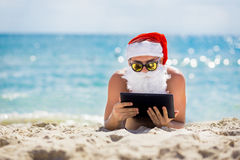 Santa Claus on the beach with a tablet in hands. Christmas, holidays, technology and people concept - man in costume of santa claus with tablet pc computer stock photography