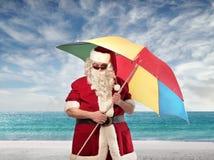 Santa Claus Beach Umbrella. Santa Claus with an opened beach umbrella on a beach stock photography