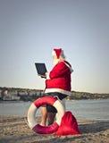 Santa Claus at the beach. Using a laptop stock image