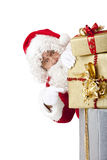 Santa Claus behind Christmas gift boxes. Santa  Claus is hiding behind a stack of Christmas gift boxes and points on them. Isolated on white Stock Image