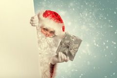 Santa Claus from behind white blank banner stock image