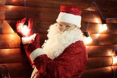 Santa Claus beleuchtet die Lichter auf dem Weihnachtsbaum lizenzfreies stockbild