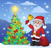Santa Claus with bell by Christmas tree Stock Image