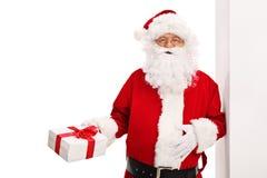 Santa Claus benägenhet mot en vägg Arkivbild