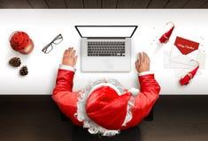 Santa Claus benutzt einen Laptop mit lokalisiert, leerer Bildschirm für Modell, Websitedarstellung stockfotografie
