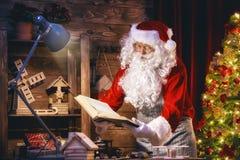 Santa Claus bereitet Geschenke vor Lizenzfreies Stockbild