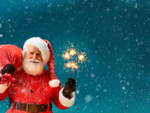 Santa Claus with a big bag of gifts and Bengal lights Stock Photo