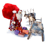 Santa Claus with big bag of gifts and his reindeer sleigh. Santa Claus carries the big bag of gifts to his reindeer sleigh to give their all people during stock photos