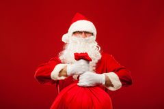 Santa claus with big bag on shoulder glasses  red Royalty Free Stock Photos
