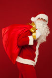 Santa claus with big bag on shoulder glasses  red Royalty Free Stock Image