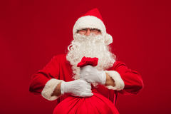 Santa claus with big bag on shoulder glasses  red background Stock Image