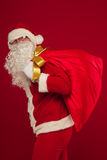 Santa claus with big bag on shoulder glasses  red background Royalty Free Stock Images
