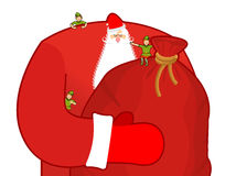 Santa Claus with big sack of gifts. Christmas elf helpers. Red b Stock Photography