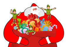 Santa Claus with big sack of gifts.  Christmas elf helpers. Red Stock Photos