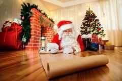 Santa Claus bij Kerstmis, Nieuwe Year& x27; s Vooravond schreef een lijst van giften t stock afbeeldingen