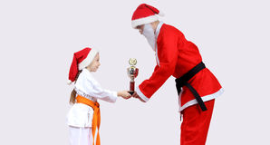 Santa Claus with a black belt is giving little girl in karategi Cup of Karate Royalty Free Stock Photos