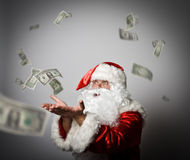 Santa Claus is blowing dollars. With best wishes for the New Year. Ironic picture Royalty Free Stock Images