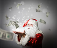 Santa Claus is blowing dollars. Stock Image