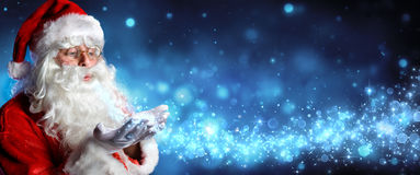 Santa Claus Blowing Magic Christmas Stars. In Snowy Night