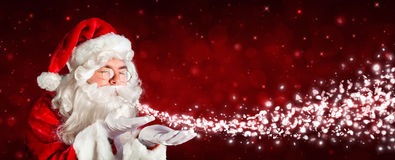 Santa Claus Blowing Snow Stockbild