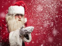 Santa claus is blowing snow flakes out of his palms Royalty Free Stock Photography