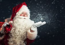 Santa Claus blowing snow of his hands. Over a dark snowy background Stock Photos
