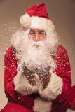 Santa Claus blowing snow to the camera. Stock Photo