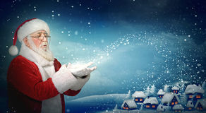 Santa Claus blowing snow to little town Royalty Free Stock Photo