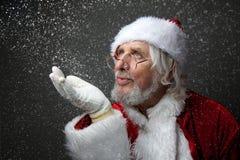 Santa Claus blows snow. Royalty Free Stock Images
