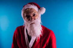 Emotional Santa Claus on a blue background. The concept of bad Santa Claus. Happy New Year and merry Christmas! royalty free stock photo