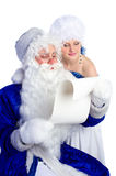 Santa Claus in blue reading list of presents Royalty Free Stock Photos