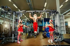 Santa Claus bodybuilder girls in Santa`s costumes at a gym on Ch. Santa Claus bodybuilder girls in Santa`s costumes at a gym workout on Christmas Day stock photos