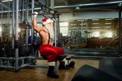 Santa Claus Bodybuilder training at the gym on Christmas Day.  Royalty Free Stock Image