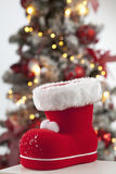 Santa Claus boot close up christmas tree in background Royalty Free Stock Photo
