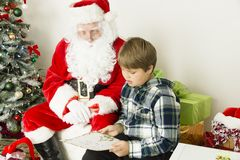 Santa claus with a boy. In the center of this horizontal image are Santa Claus and a boy.  Boy is wearing dark and light green shirt with white squares with hood Stock Photos